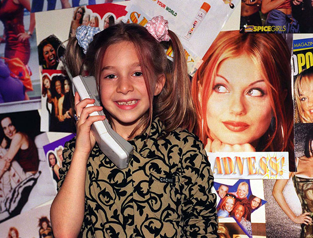 "Surrounded by posters of her favourite all girl band, Lily Stodel, uses the phone on which she had a conversation with her Spice Girl heroine, Emma Bunton last night (Saturday). ""Baby Spice"" rang the 7-year-old from Stanmore in north west London out of the blue after the youngster won a competition to speak to her favourite Spice girl in a school auction. During the 10 minute conversation, she told Lily that the girls had all been very upset about recent bad press following the sacking of their manager and said that they were not going to split up because they were very happy together'. See PA story SHOWBIZ Spice. Photo by Samantha Pearce/PA"